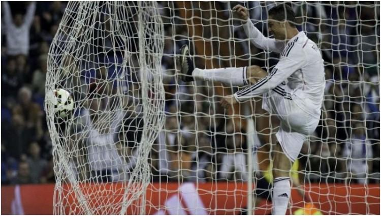 Cristiano Ronaldo menendang keras-keras bola sontekan Arbeloa yang sudah masuk ke gawang