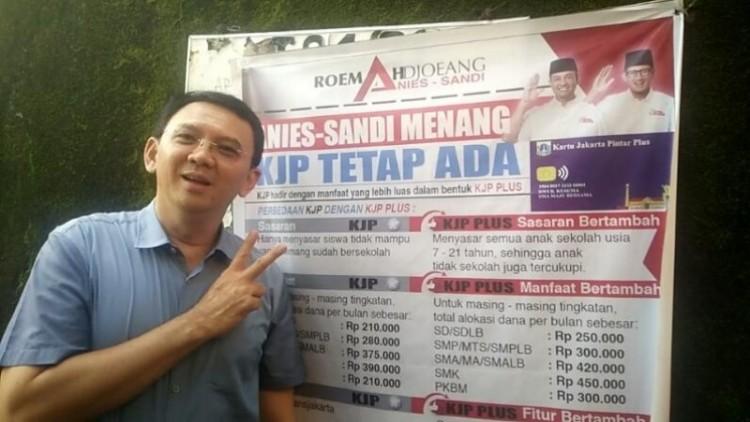 Ahok berpose dua jari di depan poster Anies-Sandi