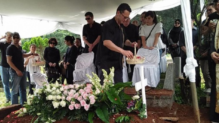Yorgos menaburkan bunga di makam Nastha Rossdiana