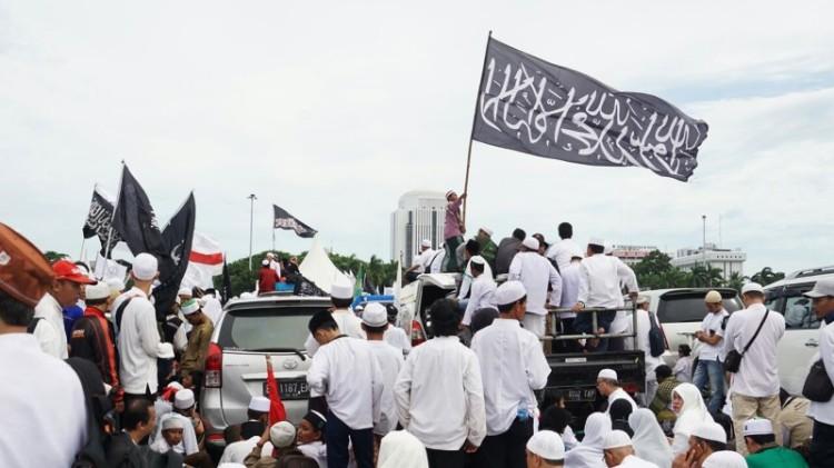 Massa aksi reuni 212 mengibarkan bendera di Monas