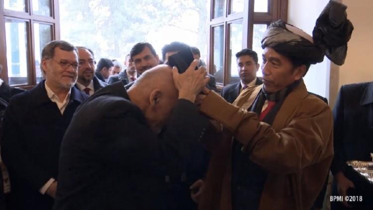 Jokowi memasangkan kopiah ke kepala Presiden Ghani