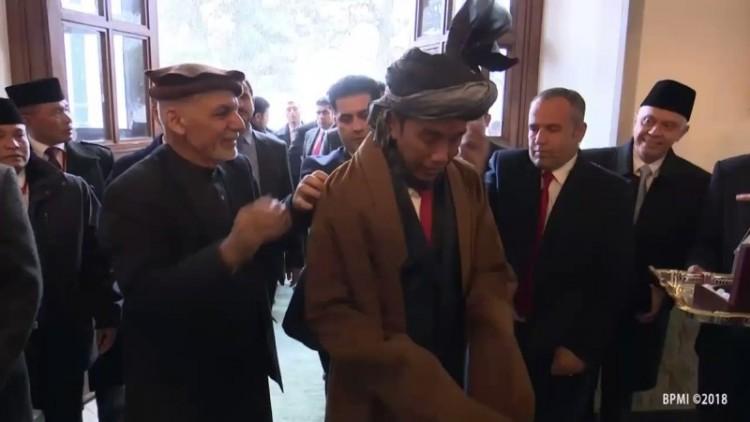 Presiden Ghani membantu memasangkan ikat kepala ke Jokowi