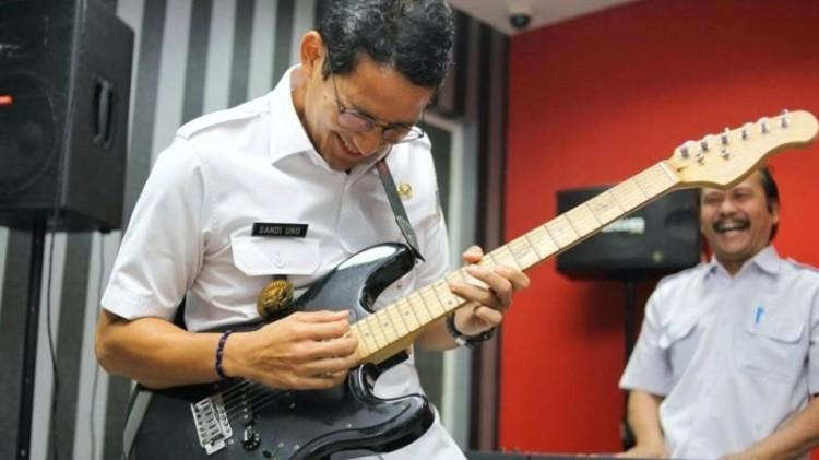 Sandiaga Uno saat bermain gitar bersama kepala BKD DKI