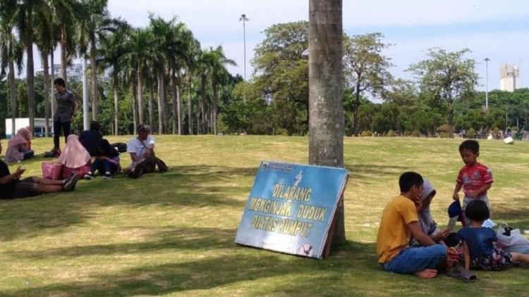 Warga bersantai di atas rumput Monas