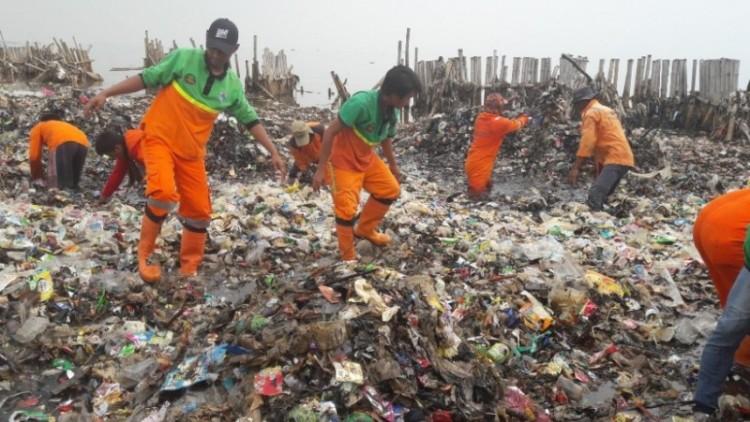 Petugas kebersihan berdiri di atas lautan sampah di Muara Angke